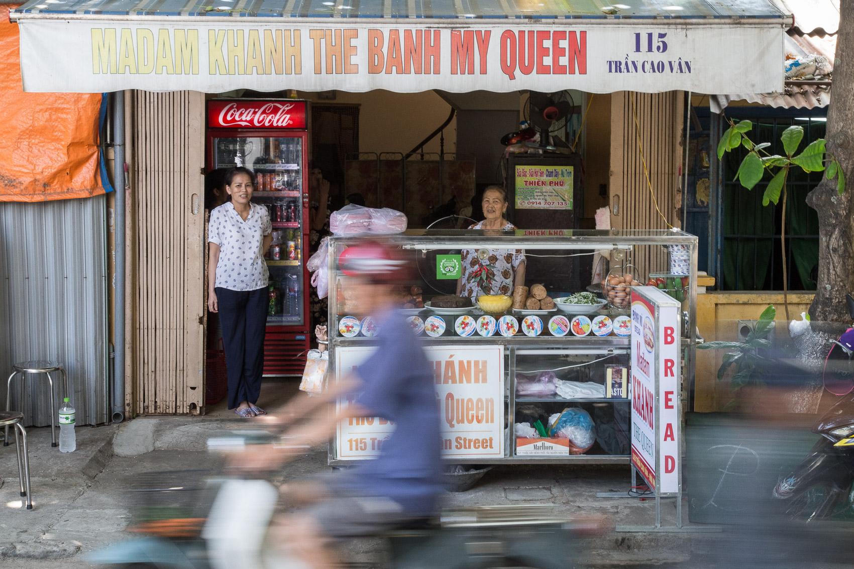 Madam Khanh (centre) behind her banh mi counter.