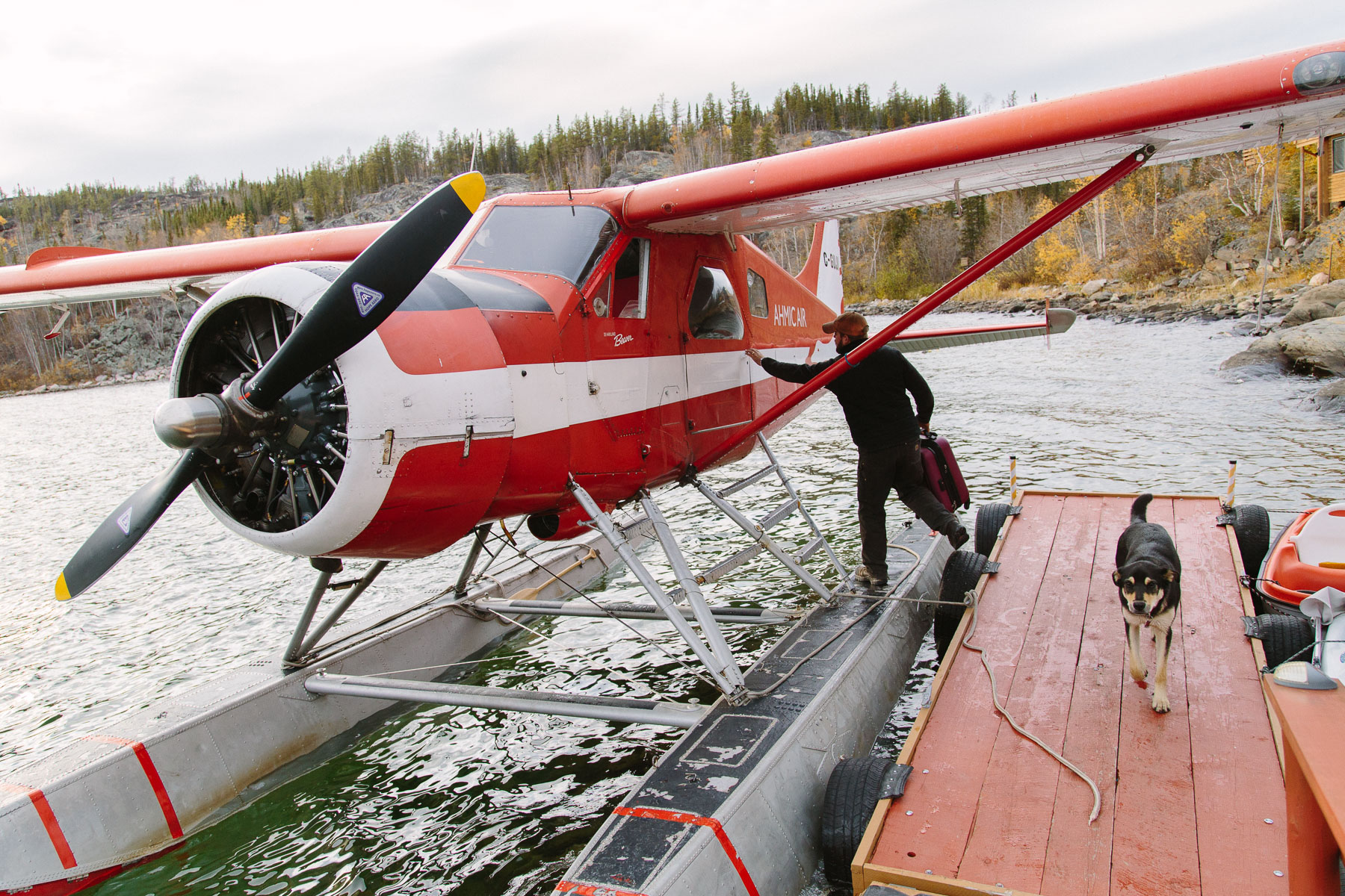 AHMIC Air pilot John Daley secures the hatch on his 1957 DeHavilland Beaver seaplane at the Yellow Dog Lodge marina, pictured with Lodge dog Jax.