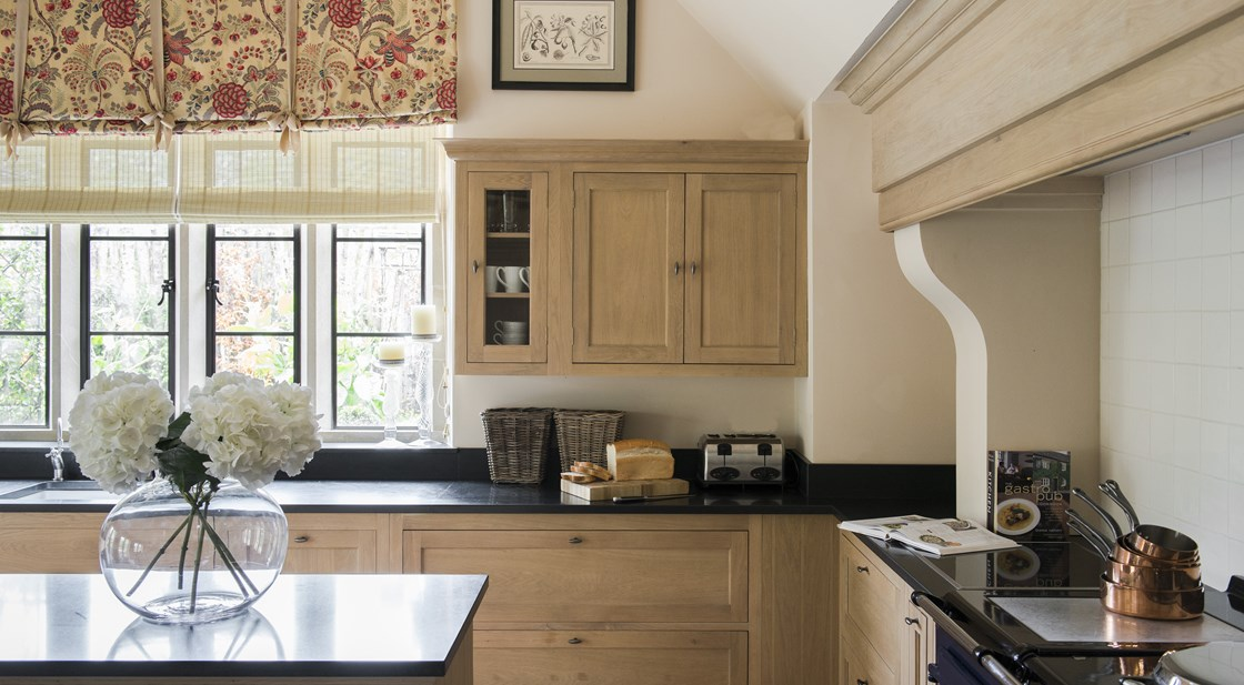 Neptune Henley Range – Kitchen fireplace with oak units and wall cabinets, dark granite worktops