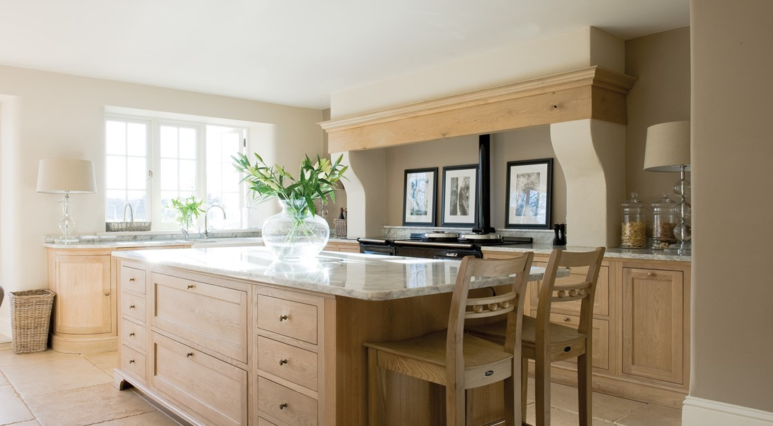 Neptune Henley Range – Central island unit in solid oak and breakfast bar with large vase and lillies