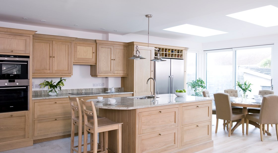 Neptune Henley Range – Beautiful side view of an open plan solid oak handmade Neptune kitchen with granite work surface and freestanding fridge freezer wall unit and wine rack