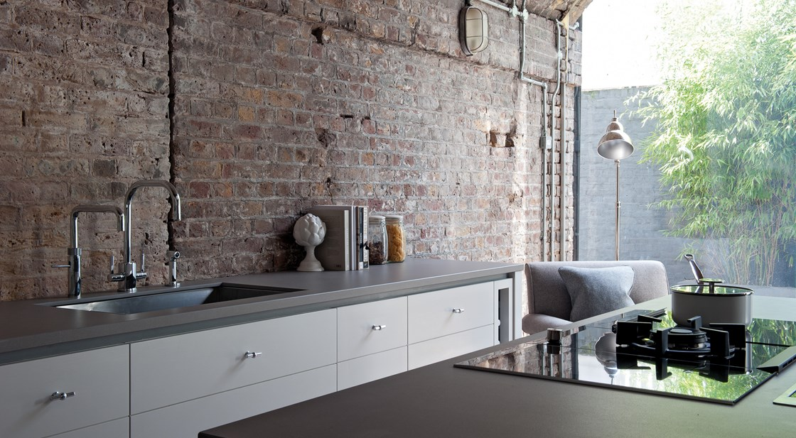 Neptune Limehouse Range – Exposed brick wall in large open plan modern handmade kitchen with central island unit and gas hob