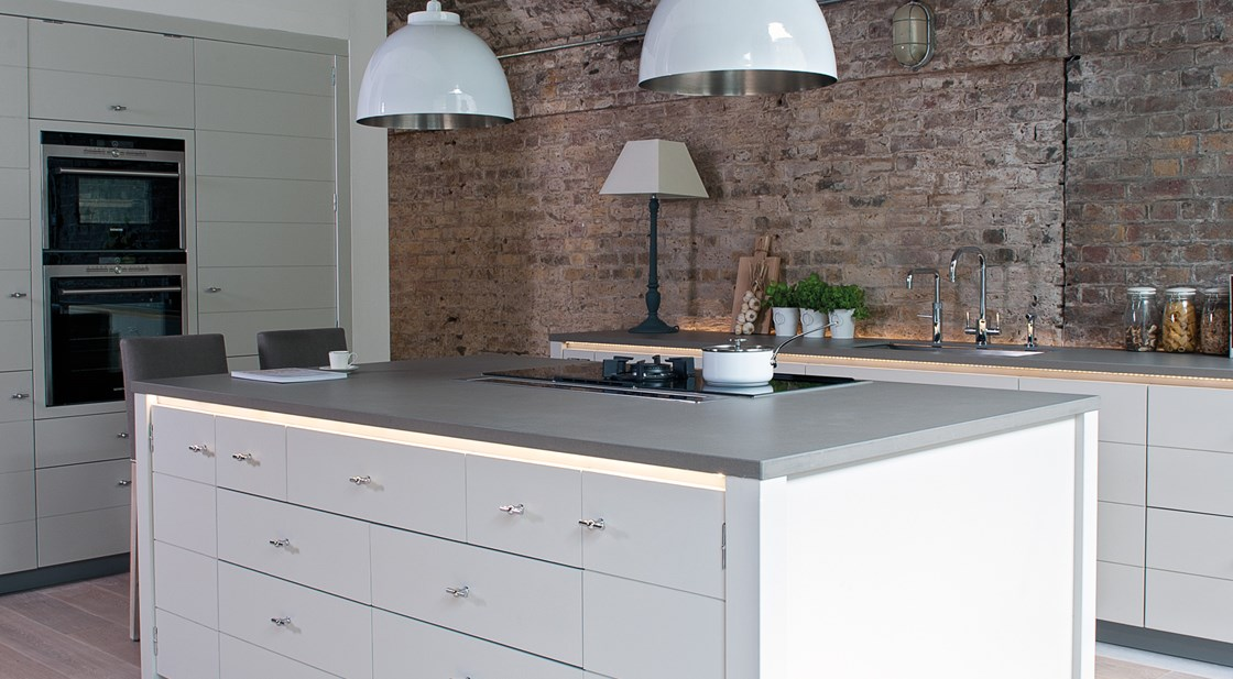 Neptune Limehouse Range – Beautiful open plan modern industrial handmade kitchen breakfast bar with overhead lamps and exposed red brick wall