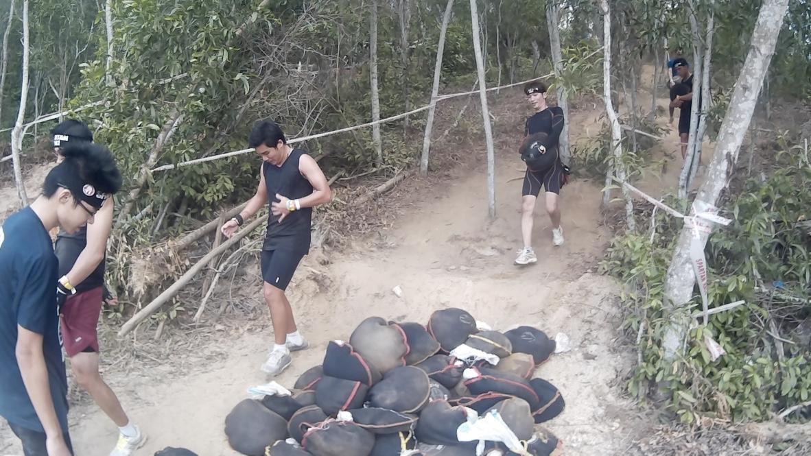 Carrying a sandbag uphill through uneven terrain.