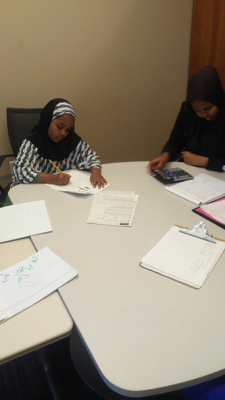 Riyana, left, works on homework, with tutor Rahma, right.
