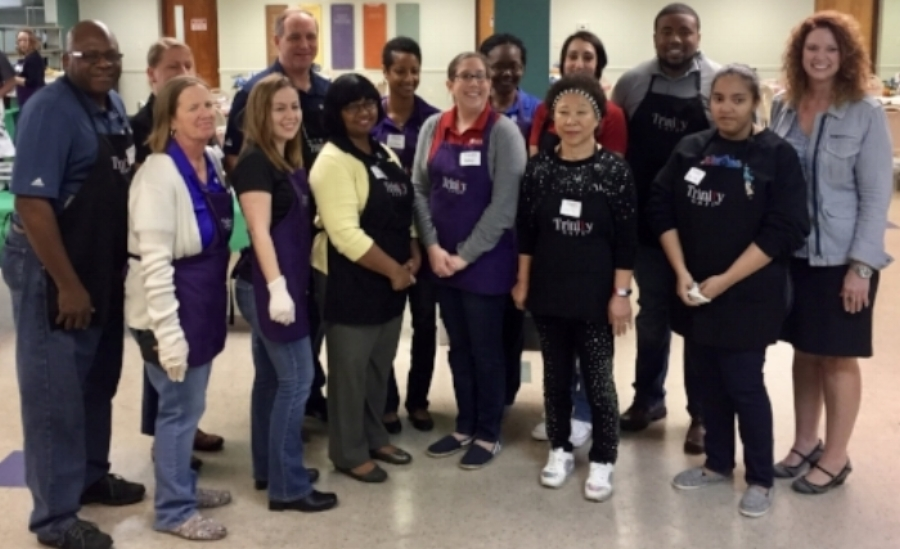 Volunteers from a local business share a group photo with Mandy Cloninger, Executive Director of the Trinity Cafe (far right).