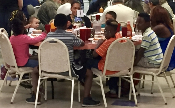 A table of children enjoy a hot meal with their parents.