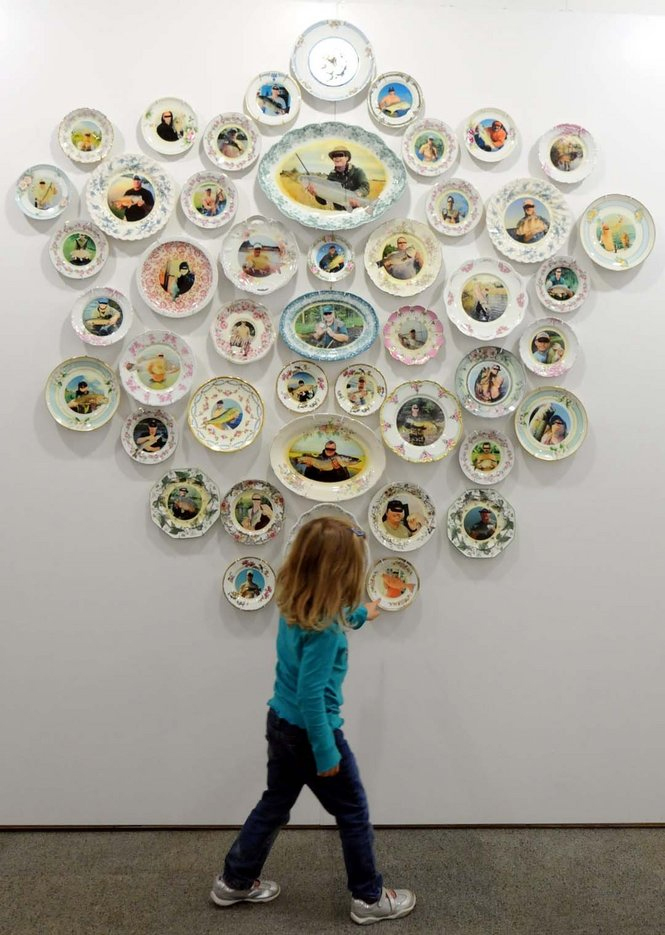 Does this make my '_____' look Big? , 2013, Wall installation of vintage dinnerware with appropriated images of fishermen and their trophies from social networking sites, 60 x 60 x 2.5 inches