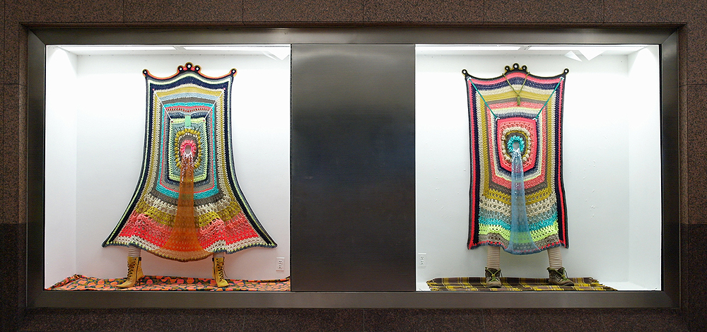 """Jester Gestures Diptych , 2016, yarn, fabric, ribbon, glitter, buttons, rhinestones, curtain ties, fabric, boots, gutter drains, pantyhose, 77""""x 78""""x 29"""" per window"""