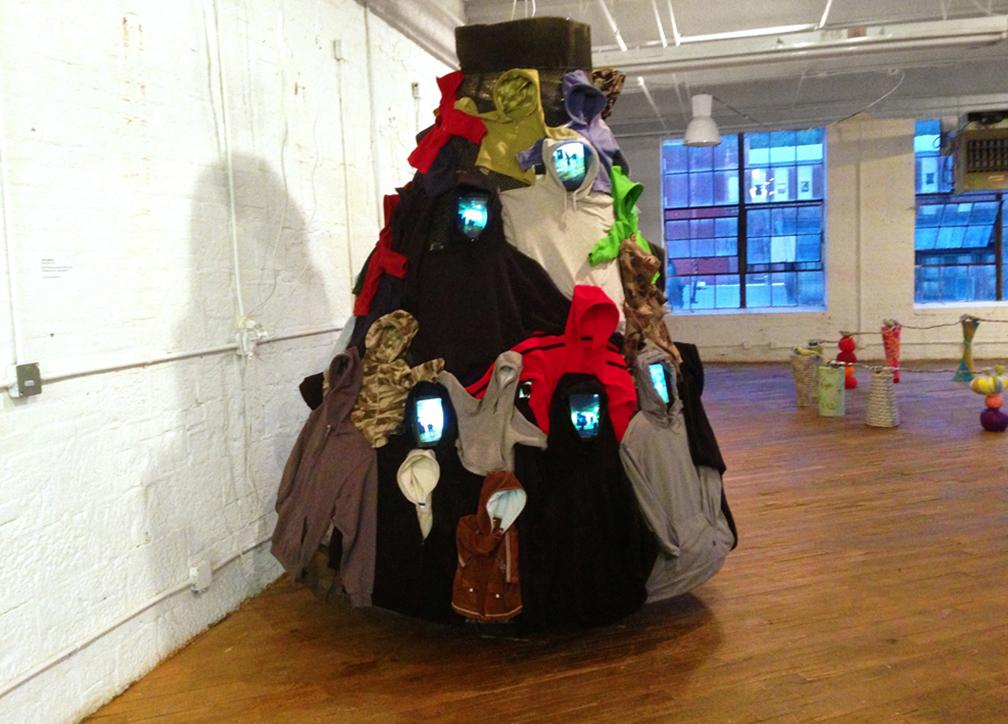 """SmartSkirt (hoodie skirt)"". Video Installation Social Sculpture, 2015. Mixed-media, 24 micro-video cameras and monitors. 84"" Diameter X 93"" H."