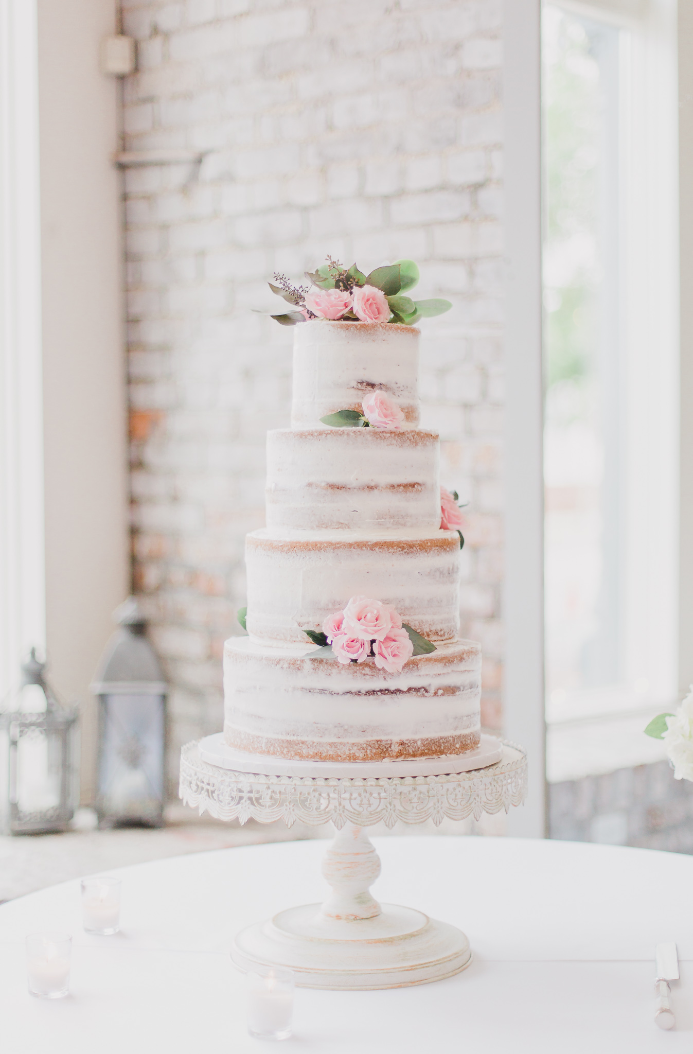 4 layer naked cake with pink roses and succulents in 5eleven venue in Pensacola, Florida
