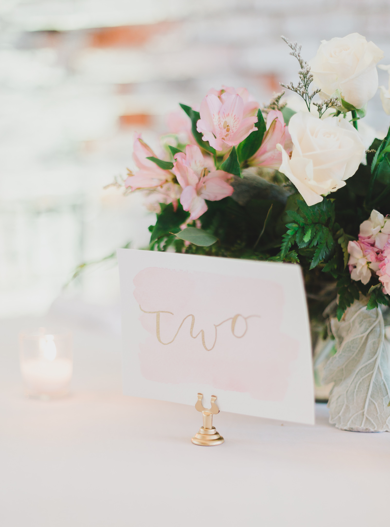 "reception table in 5eleven wedding venue in Pensacola, Florida with blush and gold calligraphy tag of the word ""two"""