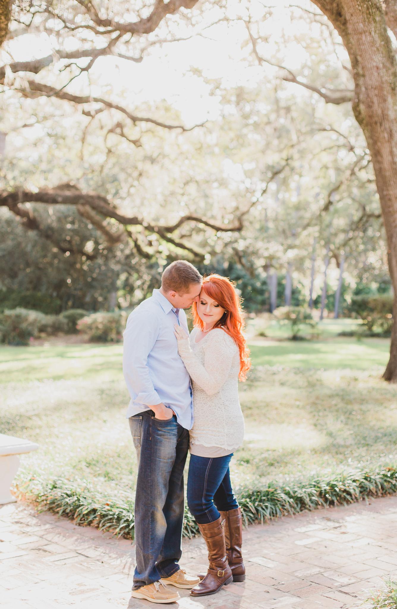 Engaged couple standing under trees in eden garden state park
