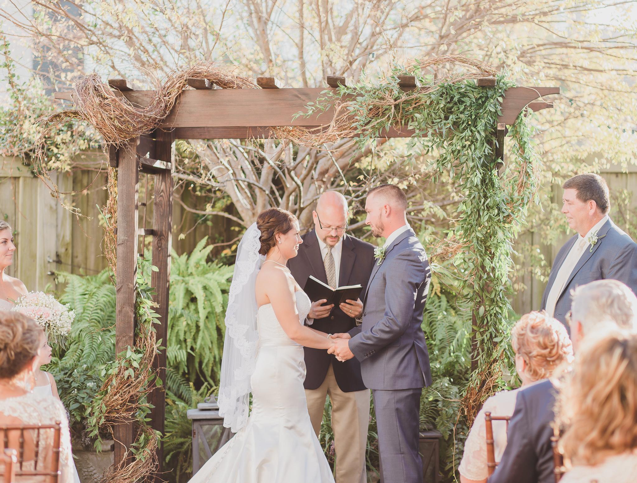 bride and groom under wooden arch in rustic 5eleven wedding venue in pensacola
