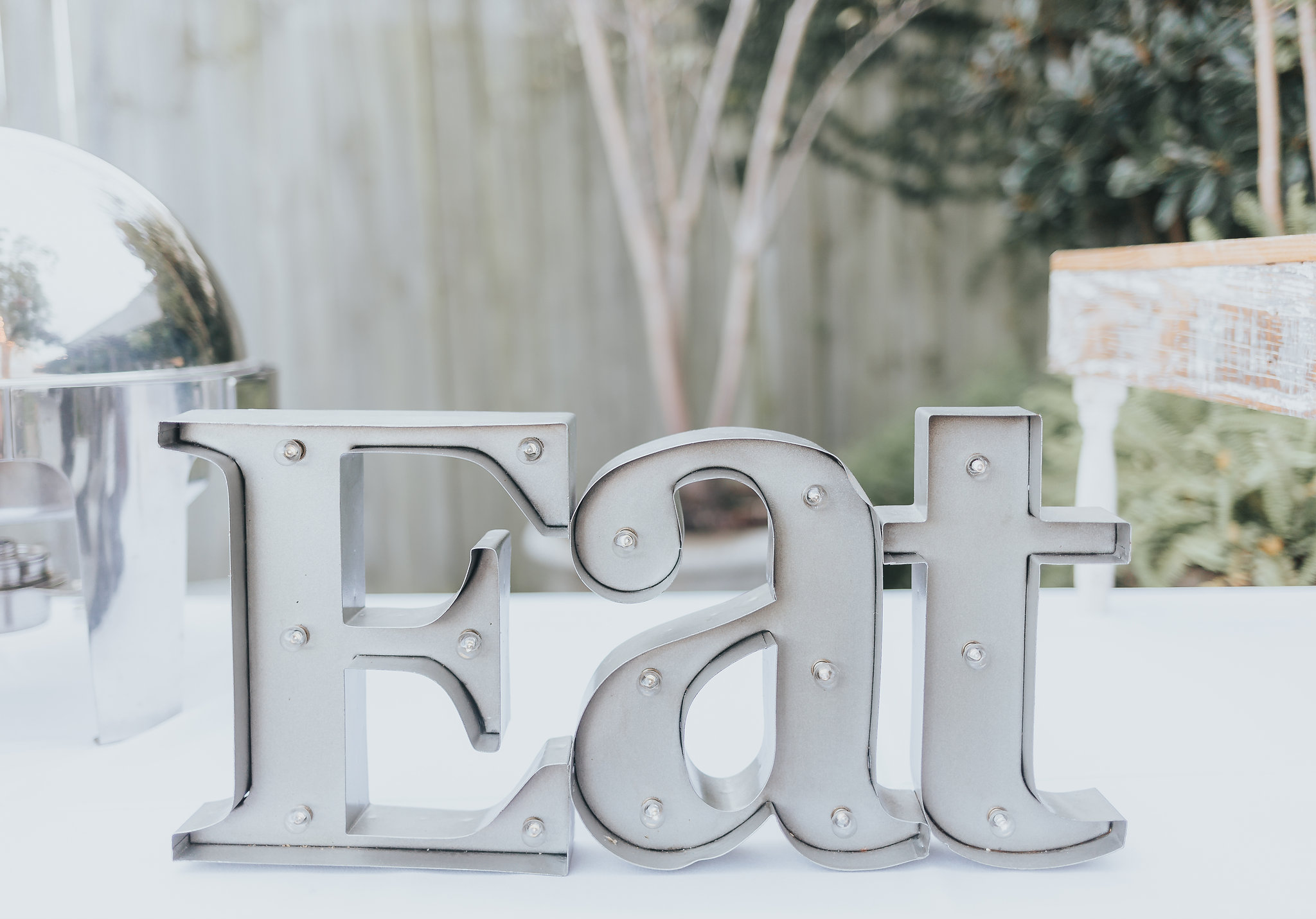 """Metal """"Eat"""" sign at 5eleven wedding venue in downtown pensacola"""