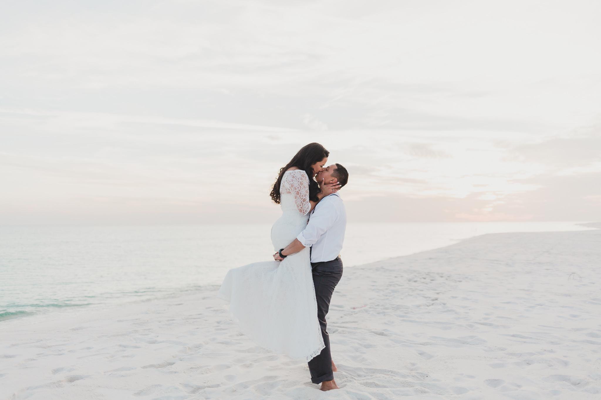 bride carrying groom pose on pensacola beach