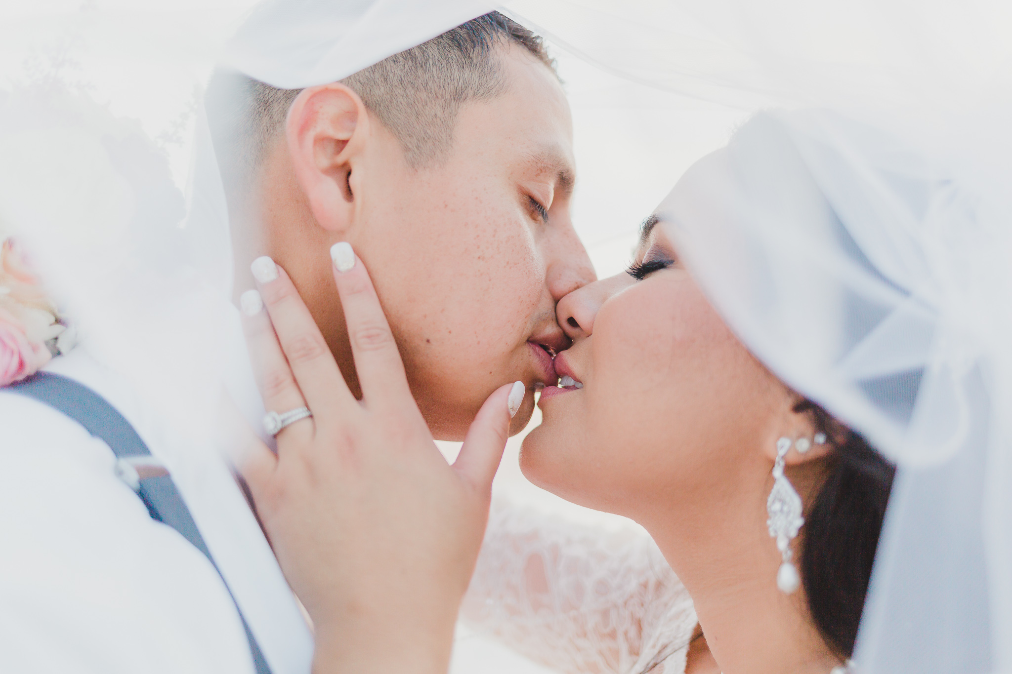 under the veil bride and groom portraits