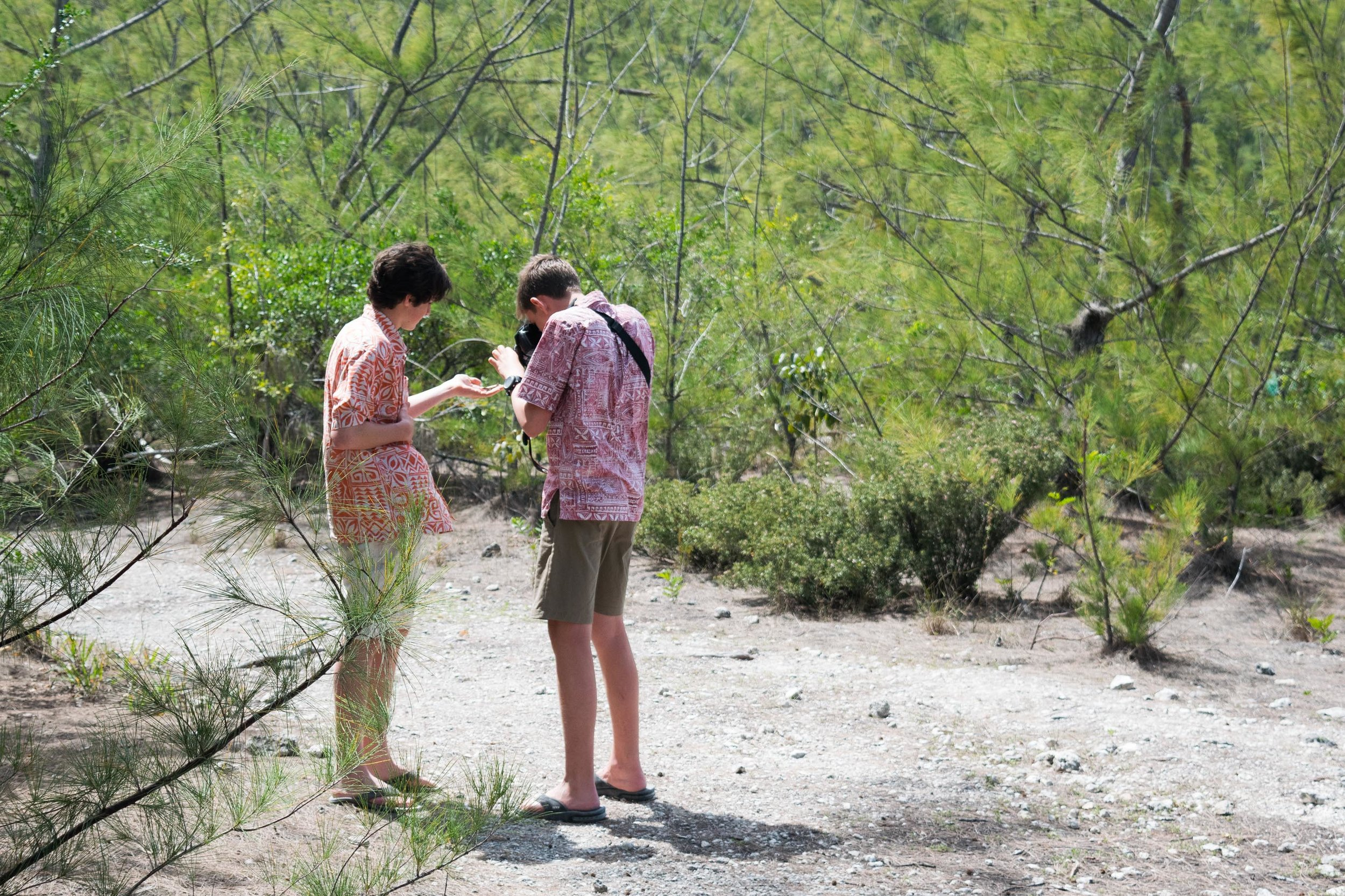 Students Sawyer and Patrick getting up close with a lizard.