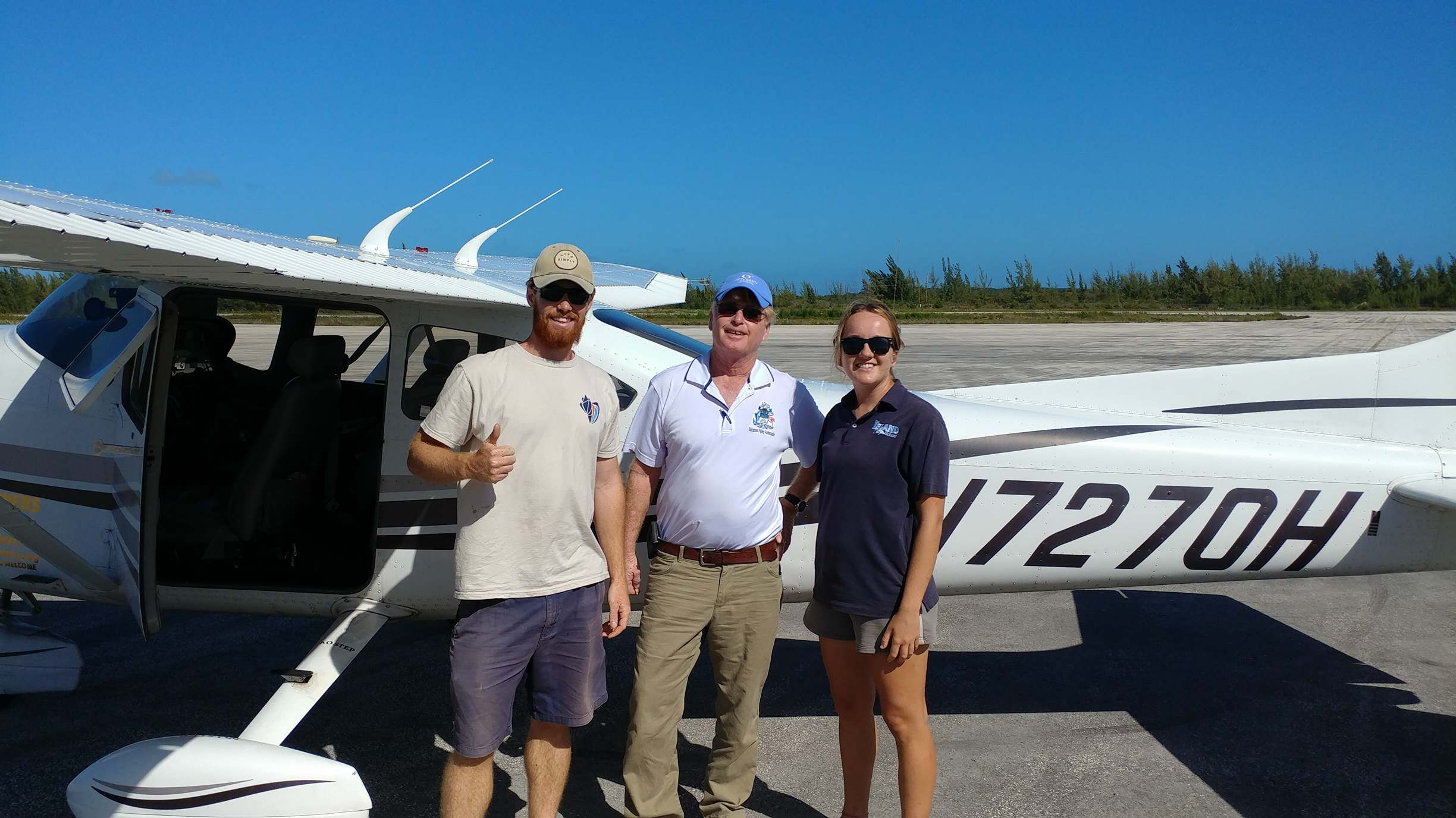 CEI researchers Eric Schneider (left) and Danielle Orrell (right) waving off Mark M. Steinberg (middle, pilot) transporting the samples to the US for analysis.