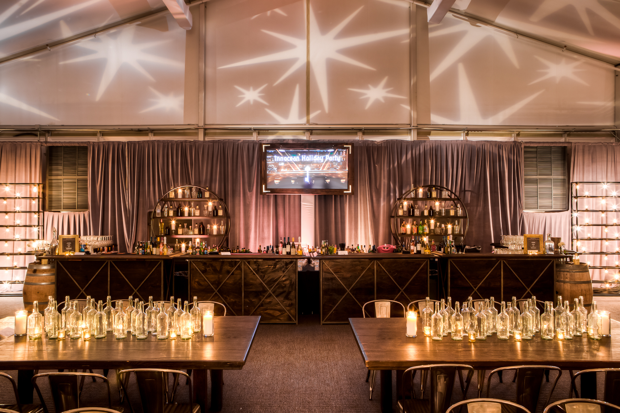 orange county corporate event planner speakeasy lit bottles on wood tables