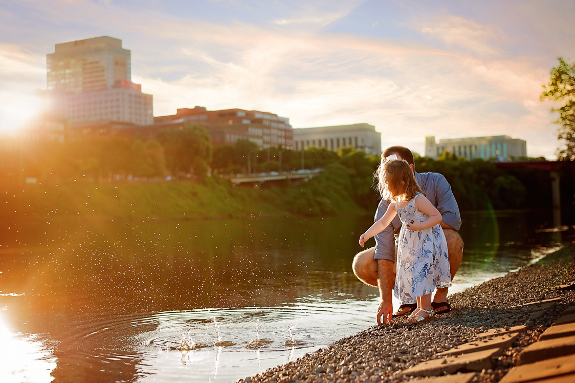 Daddy and daughter skipping stones in the Cumberland River, Downtown Nashville, TN. AluraWayne Photography