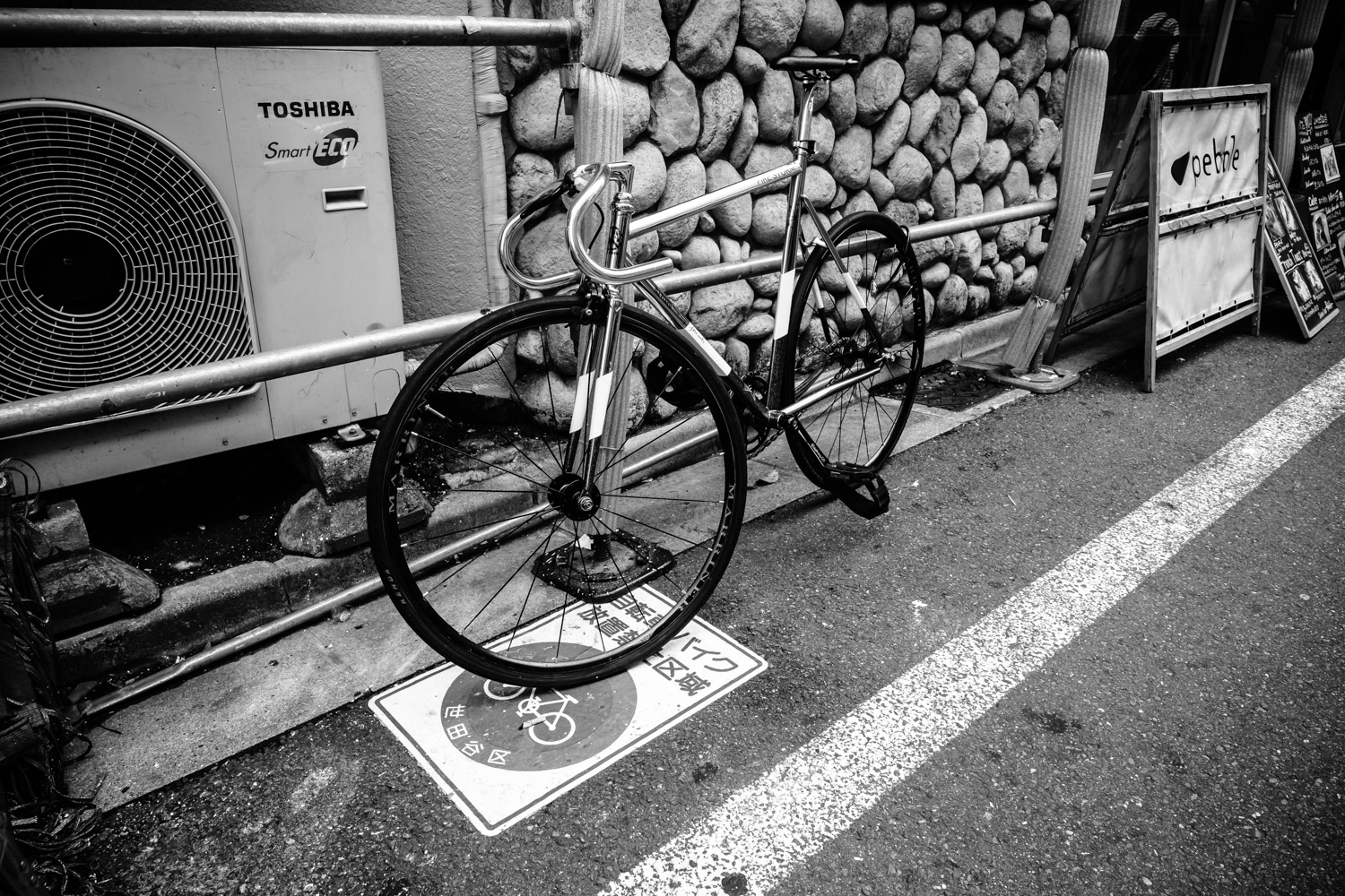 """The sign on the road says, """"No bicycle parking"""""""