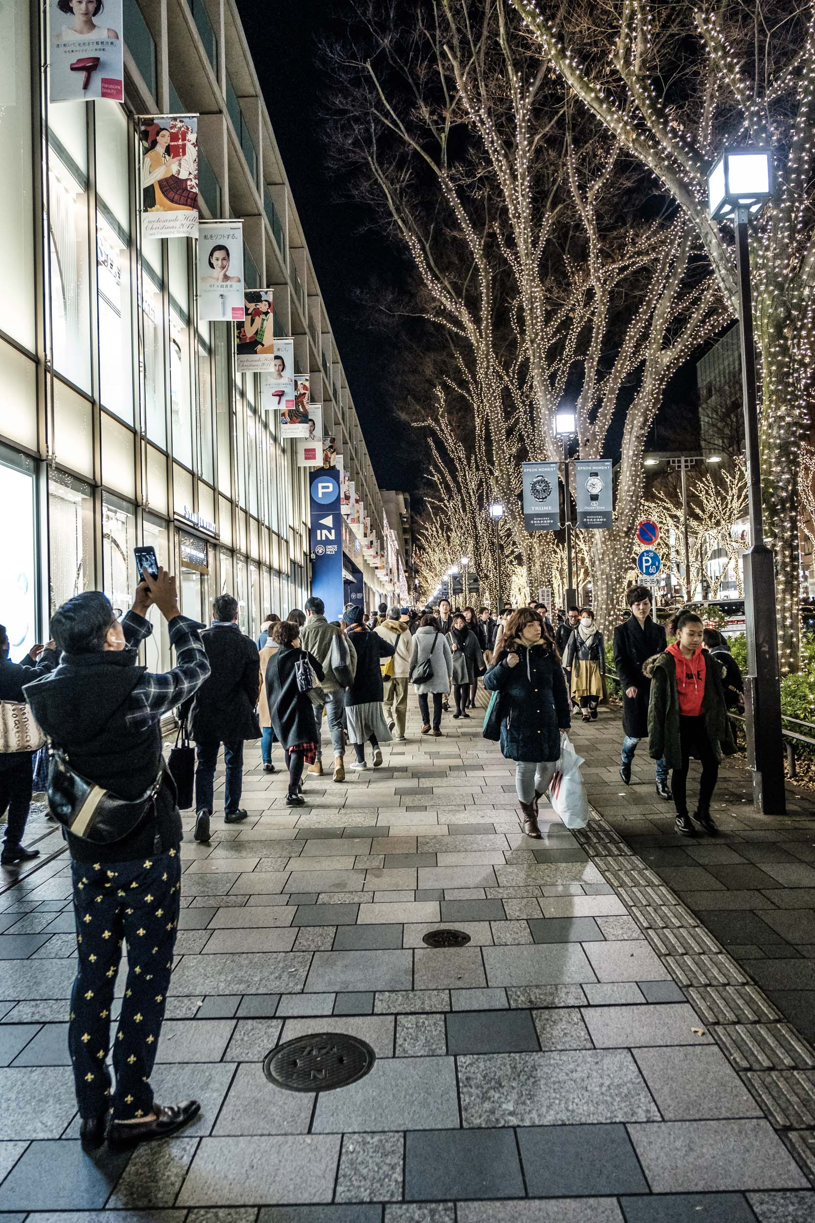 People pass in front of Omotesando Hills
