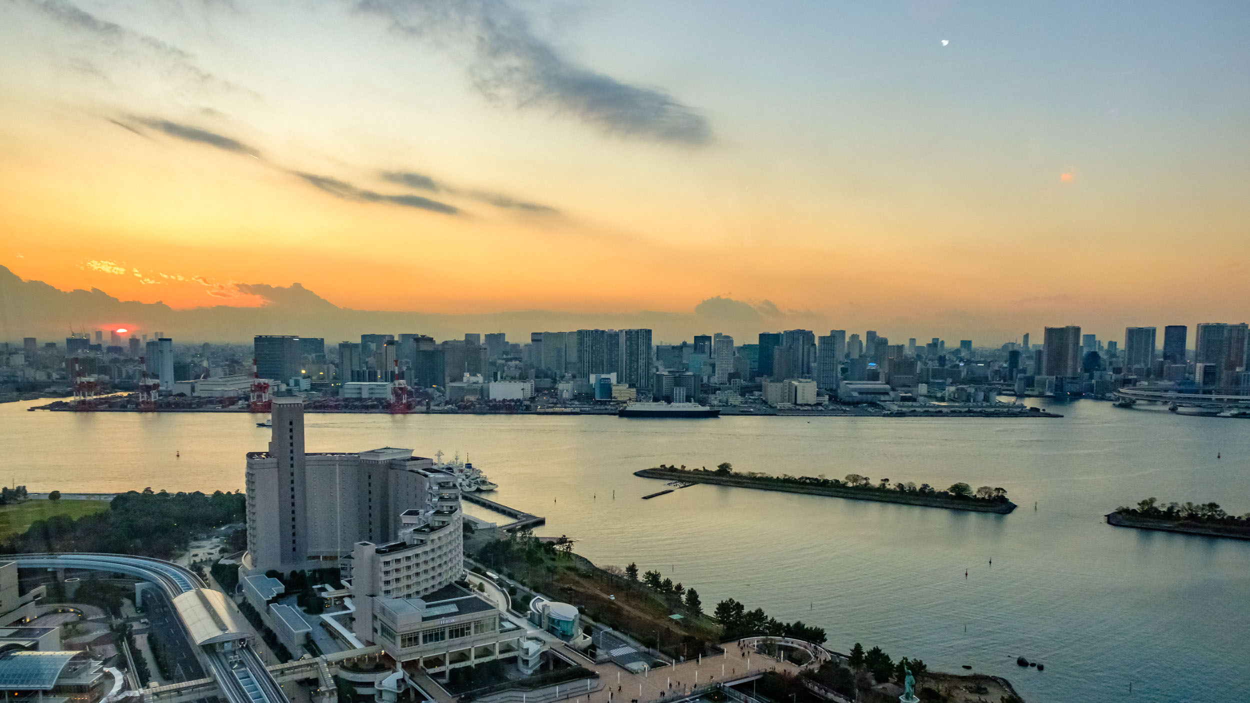 On the other side of the bay is the Shinagawa port area. Where the sun is setting is the approximate location of Mount Fuji. The building in the foreground is Hotel Nikko