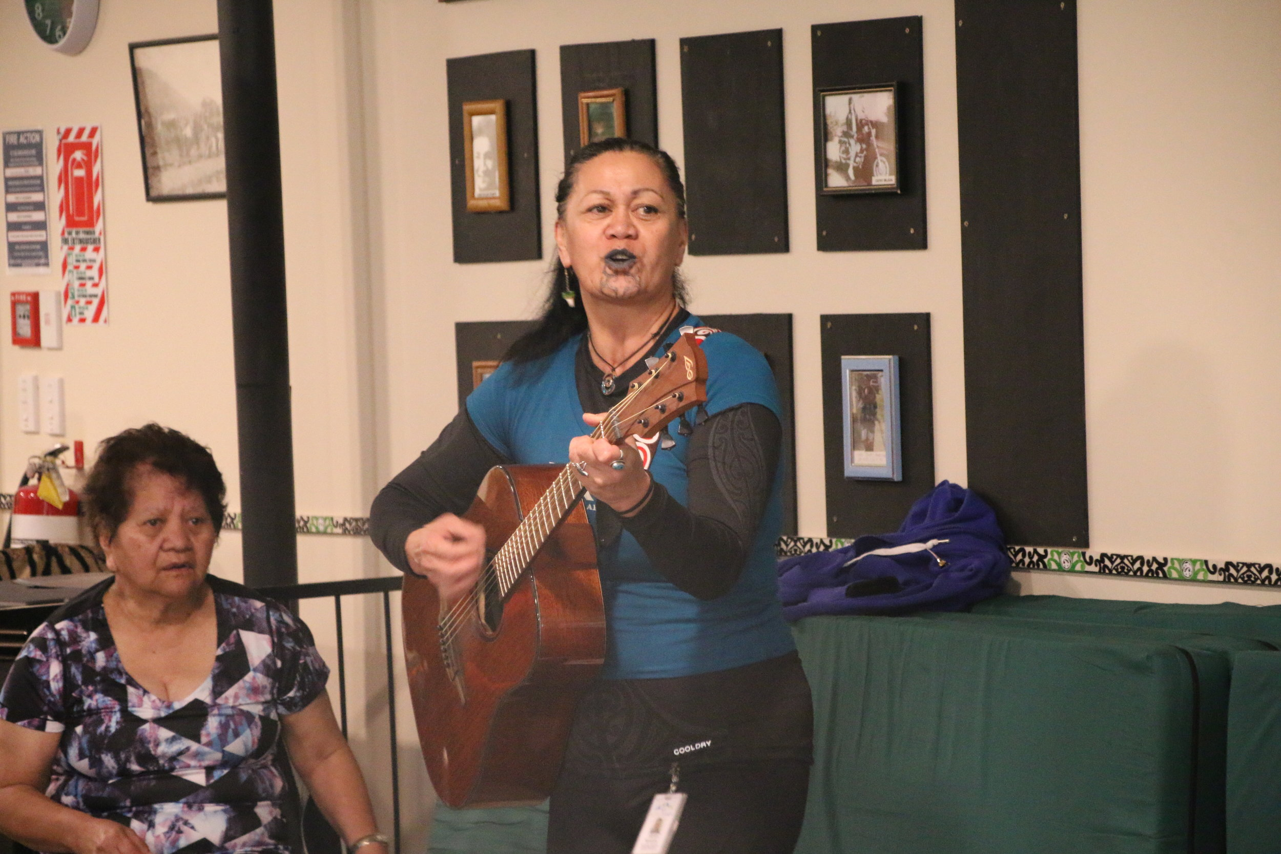 A slight technical issue led to the good ol' guitar as a fill in during Noho Pakari/Tu Kaha. Sharlene Maniapoto plays under the watchful eye of Whāea Erana Maxwell