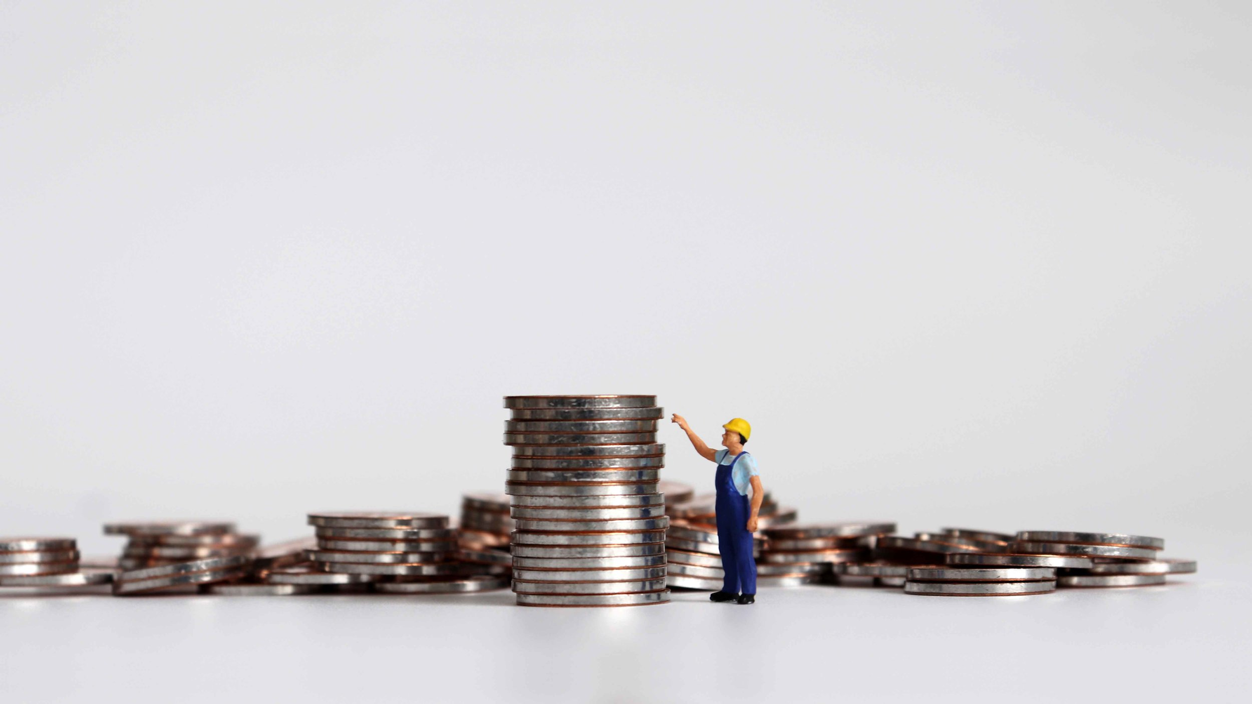 A-miniature-worker-pointing-at-a-pile-of-coins.jpg