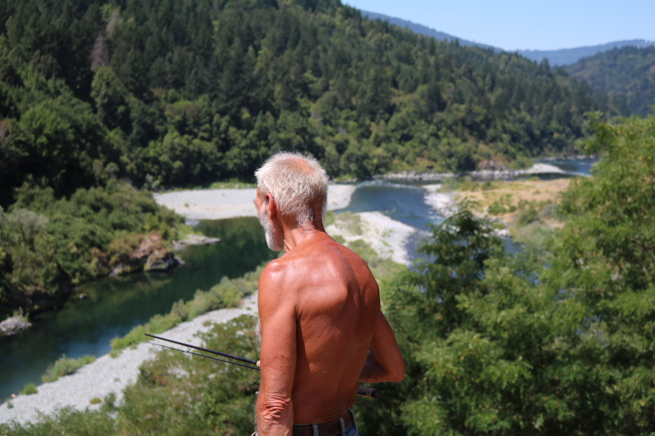 An old salmon fisherman searches for moving shadows above the confluence of the Trinity and Klamath Rivers