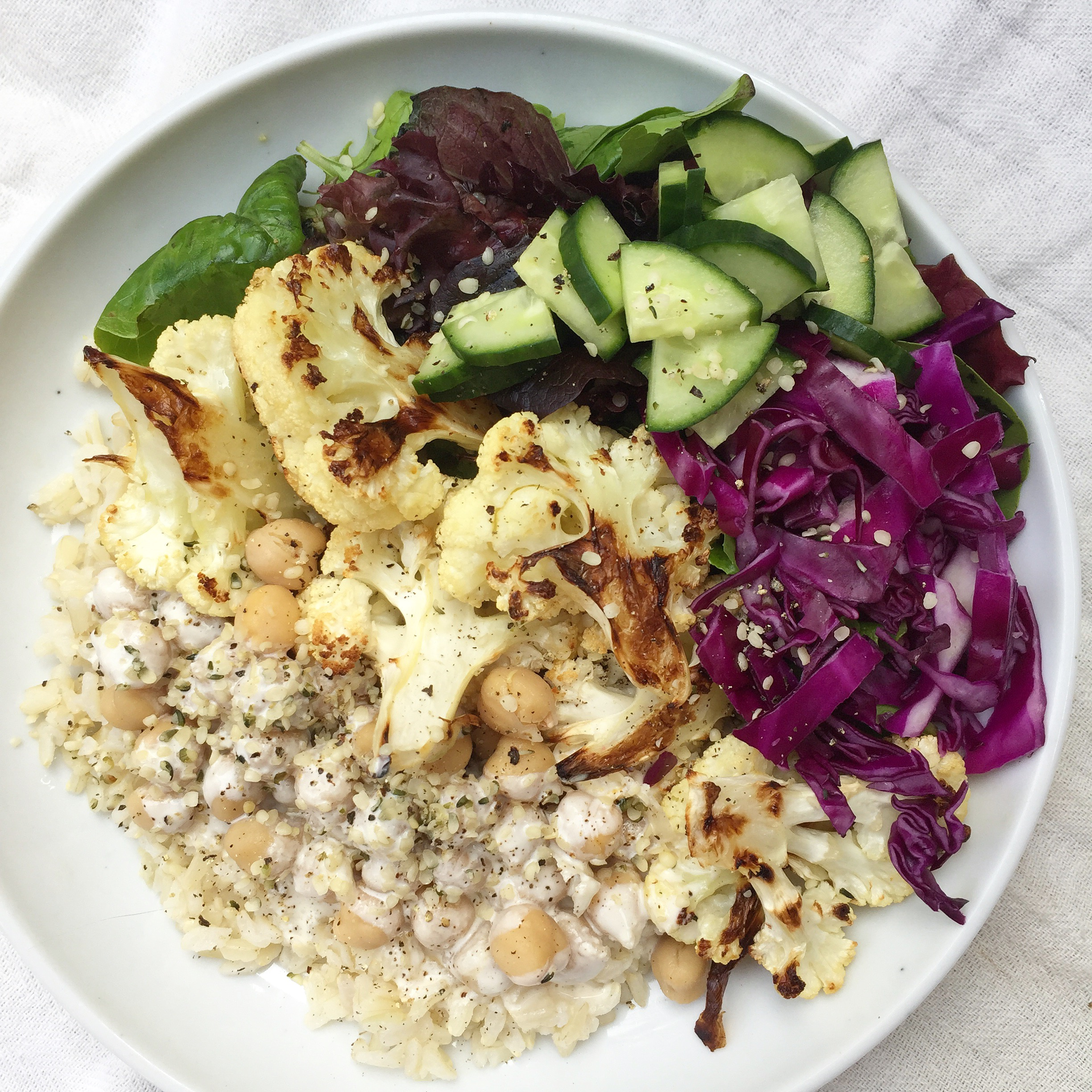Middle Eastern-inspired bowl with brown rice, chickpeas, roasted cauliflower, raw red cabbage, cucumber, baby lettuce mix, creamy garlic sauce, hemp seeds, and fresh cracked pepper.