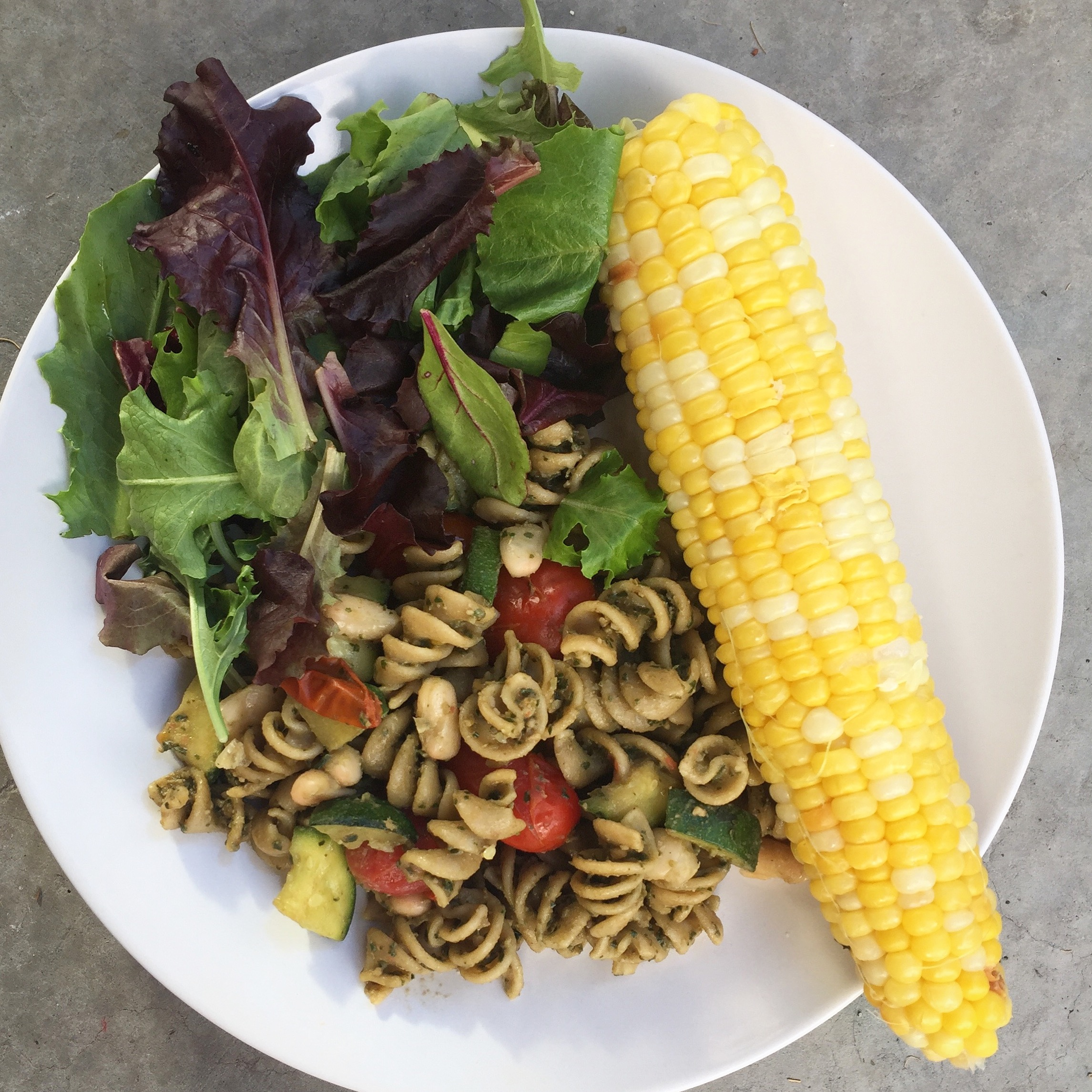 Pesto on kamut rotini with white beans and tomatoes; in-season corn; mixed greens