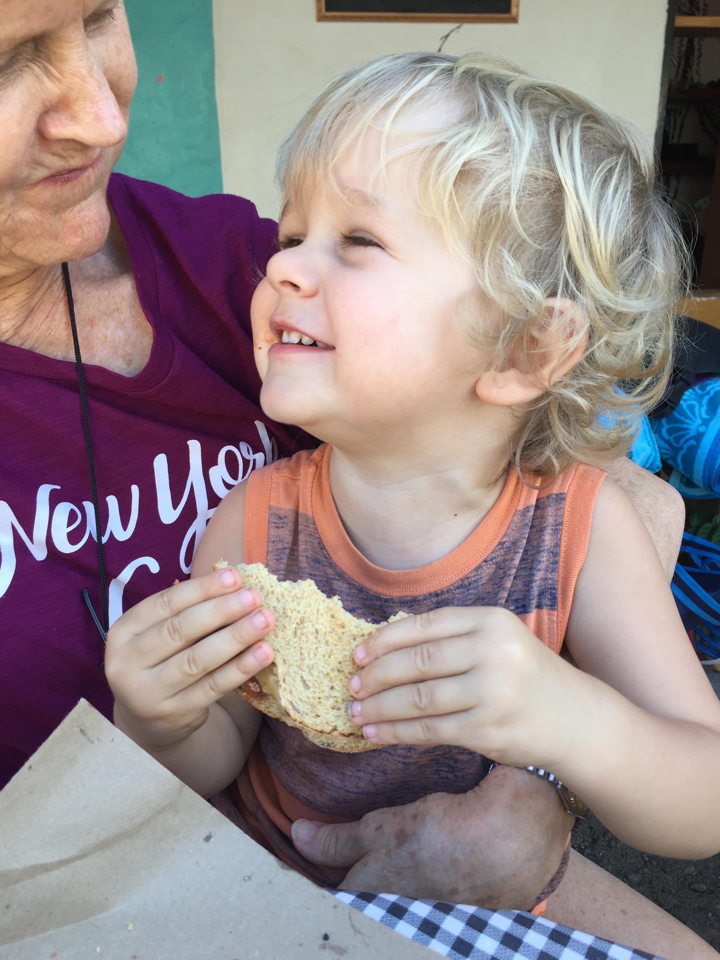 Alister on Grandma's lap enjoying one of Cilantro's sandwiches.
