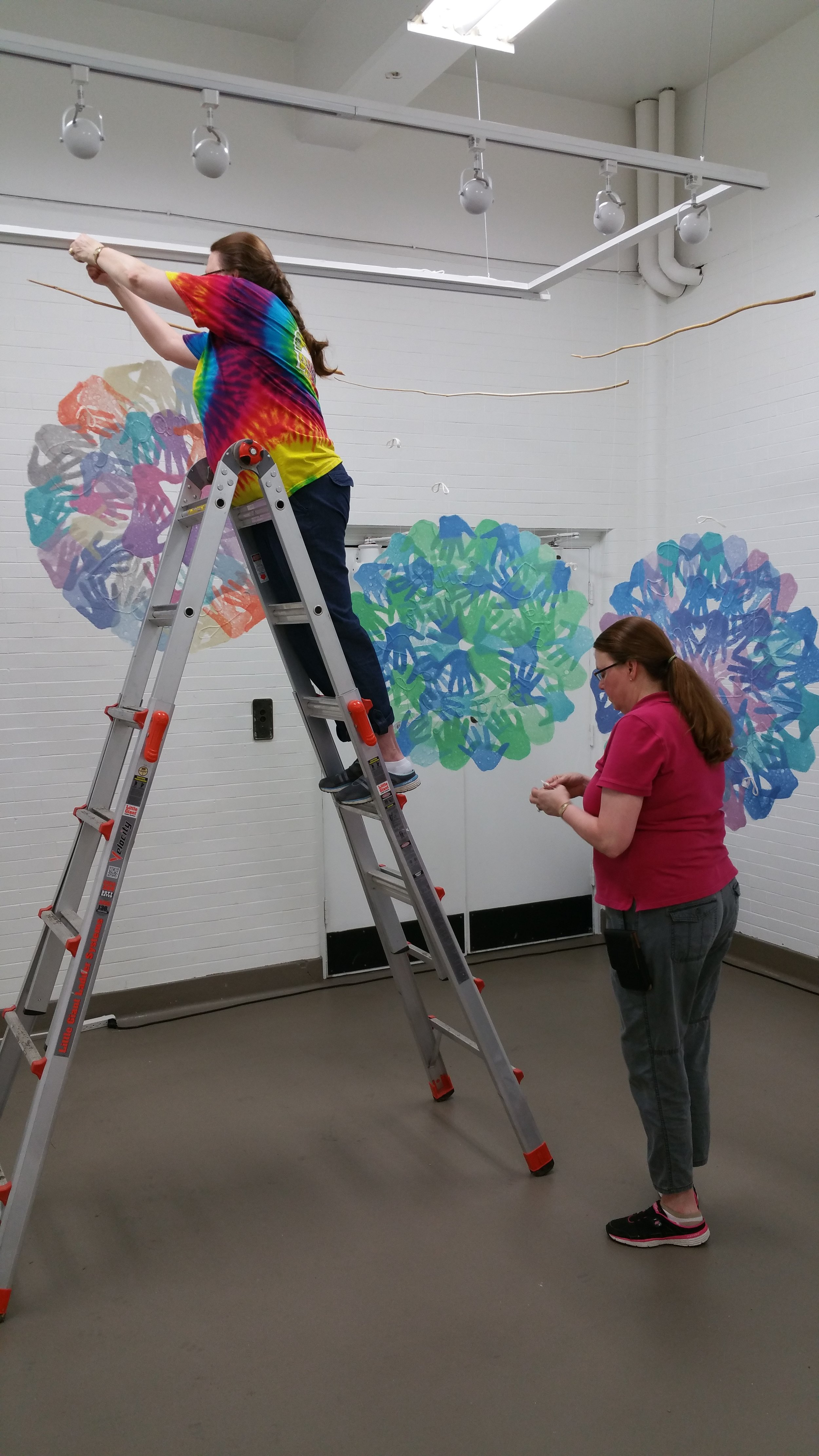 Veda and Meda Rives install three pages of their hand-made paper pieces, Inner Circle.