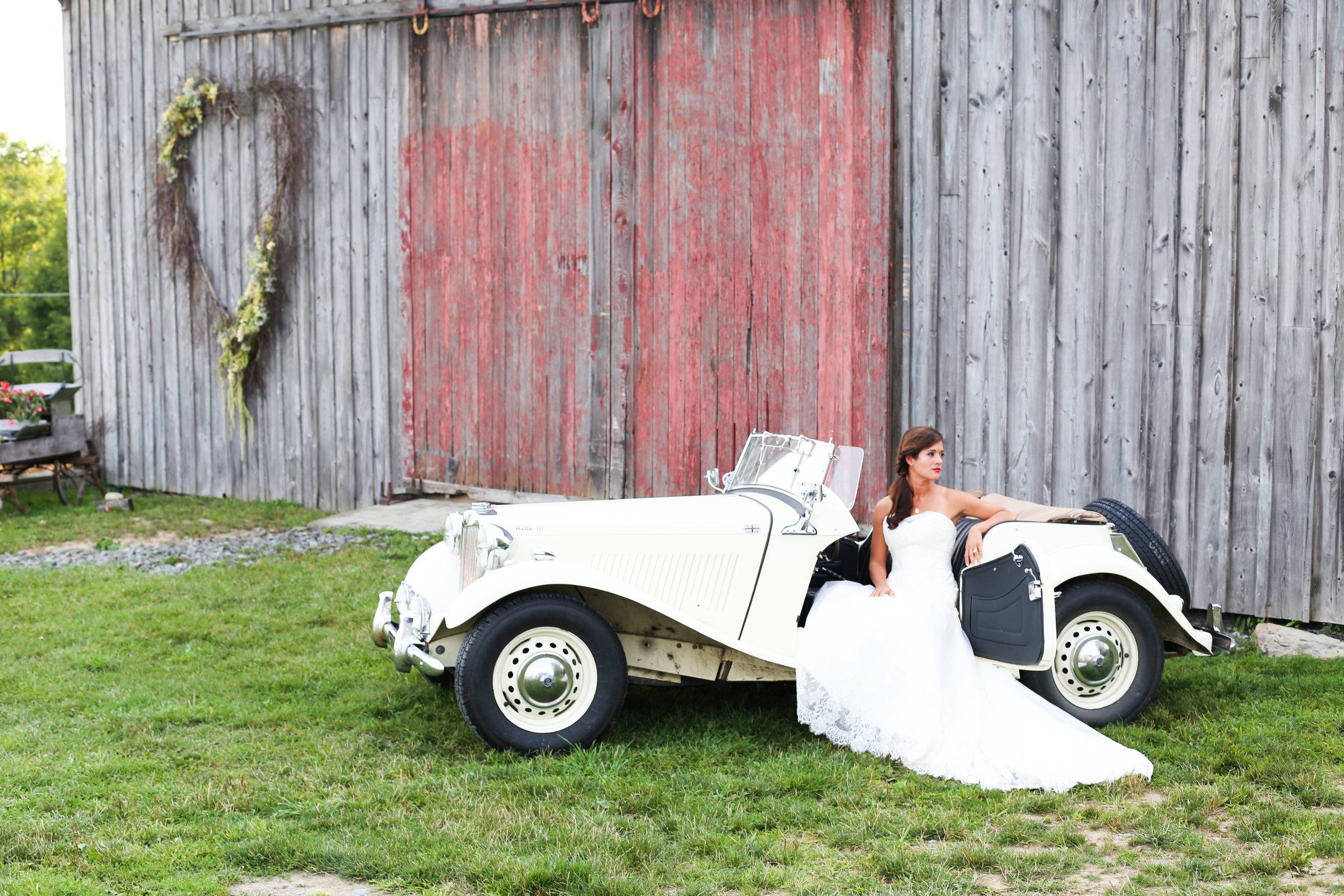 bride posting on vintage car in front of barn at Fiddle Lake Farm in PA