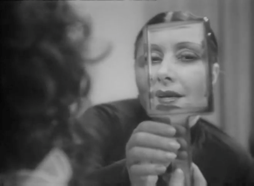 Figure 2. Charlotte holds up her mirror, replacing Frau Fesse's face with her own.
