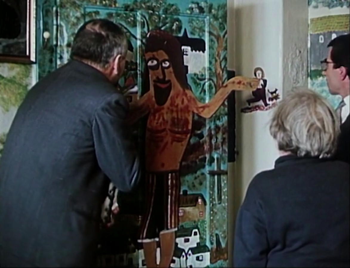 "Officials from the National Insurance inspect a homemade painting of Jesus on the cross in ""The House of Joy."""