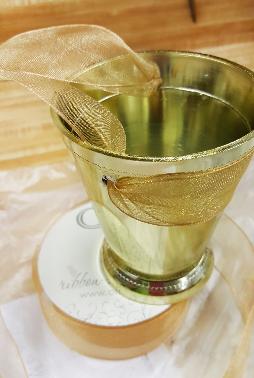 Next, thread your favorite   wired   ribbon through the holes. We like ours to be on the outside of the front of the cup, to give it the most stability preventing anything from spilling forward.Wired ribbon works best, as it will not slip or slide as you tie the ribbon securely to the chair.