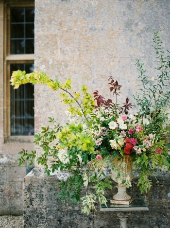 A large urn can do multiple jobs. Use it during your ceremony and then move it to the reception. This fascinating piece holds your attention with multiple colors of foliage, foxgloves, dahlias and cosmos.