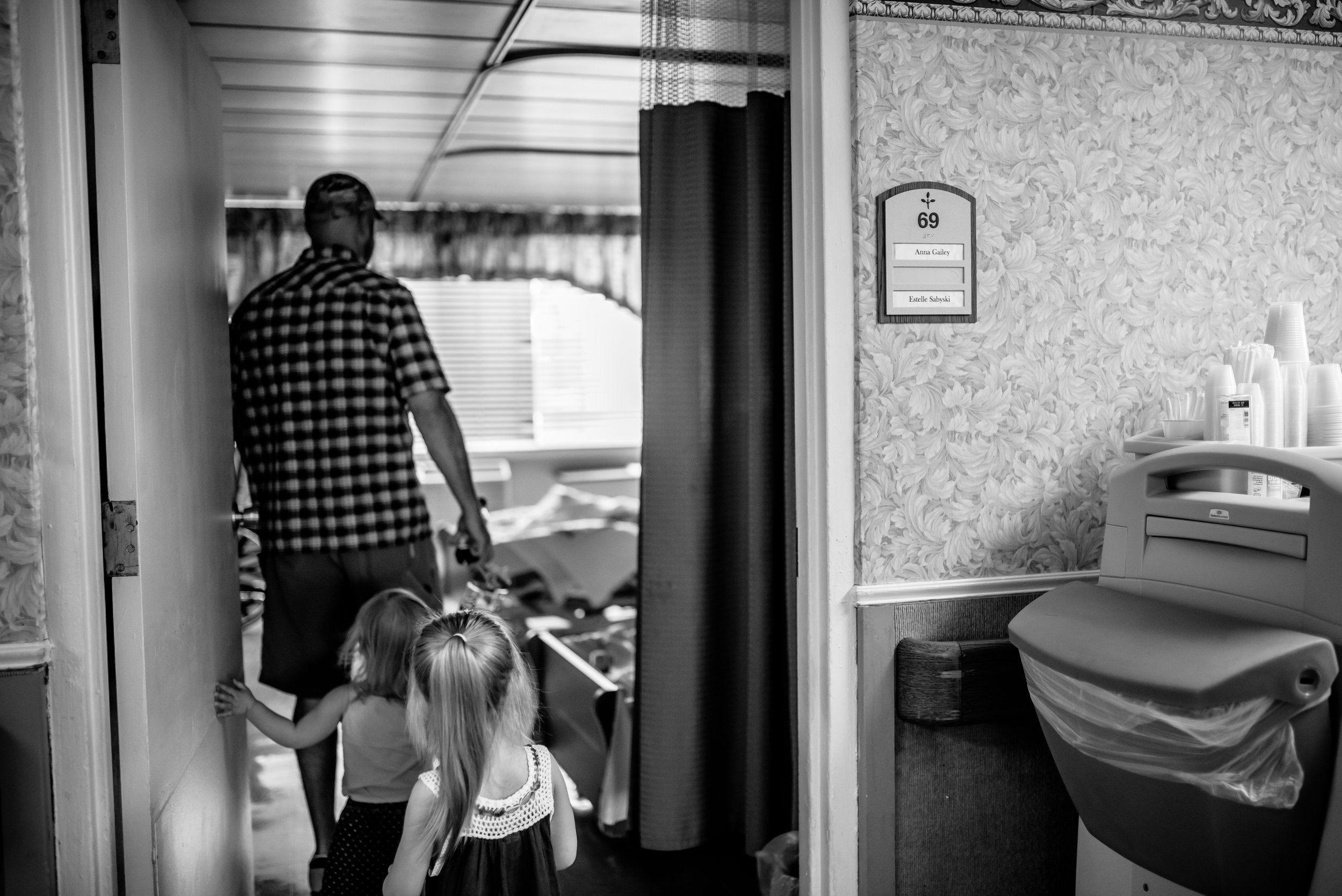 Dad and daughters entering room of nursing home