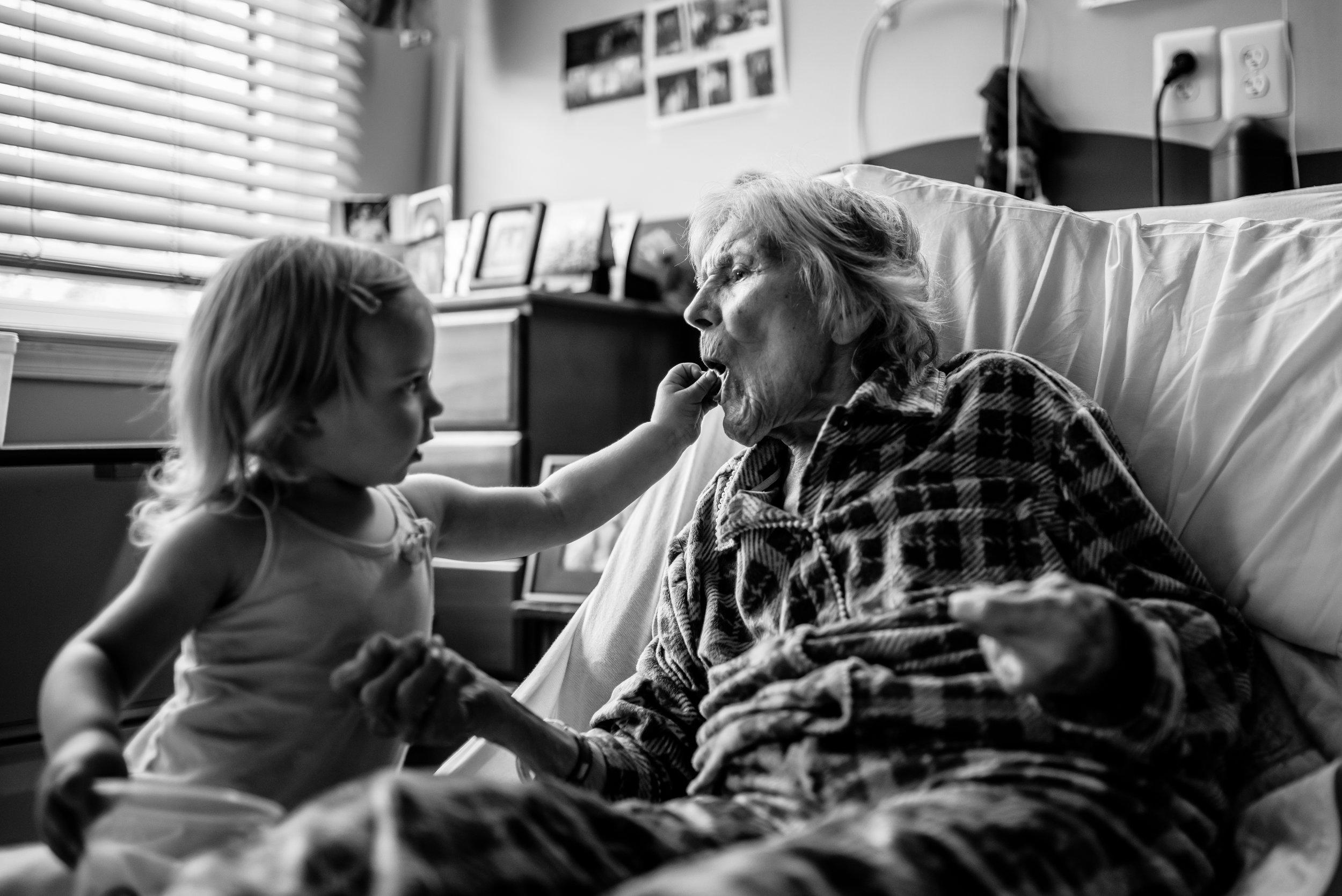 Girl feeds pretzel to great-great-grandmother