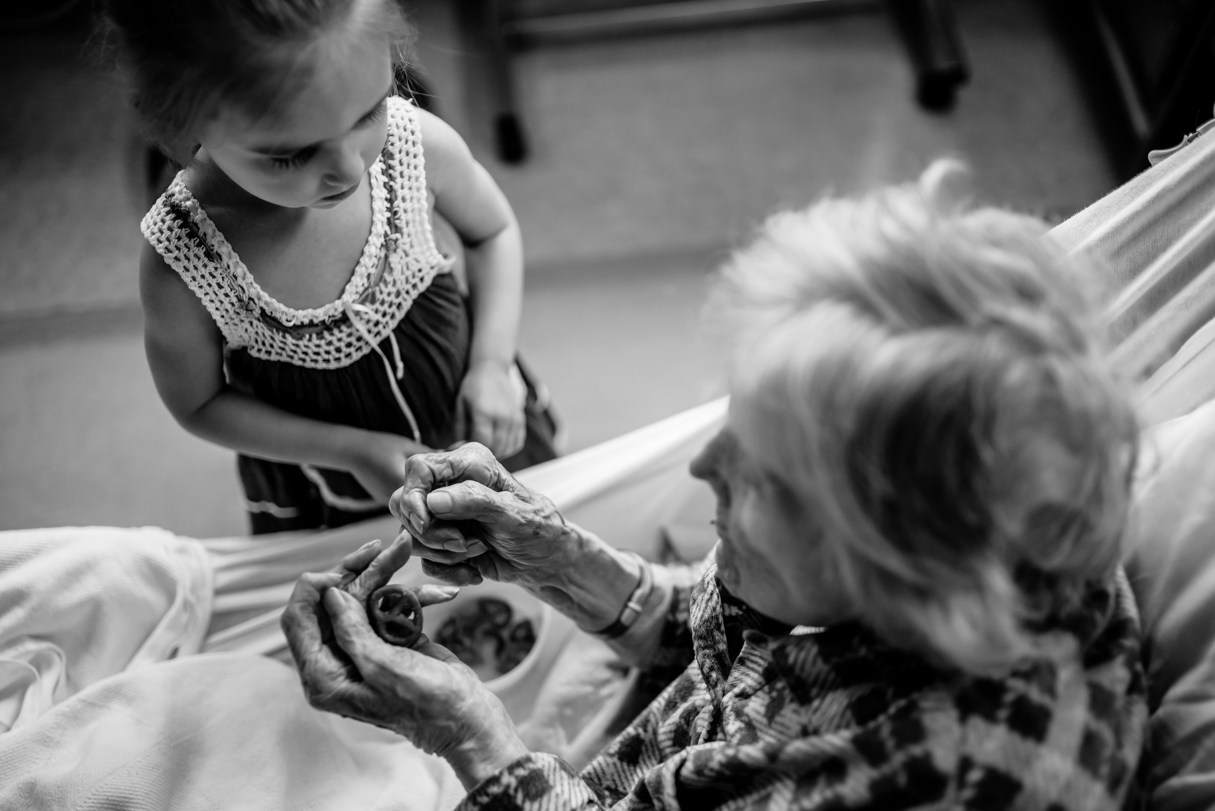 Girl looks at great-great-grandmother with pretzel in hand