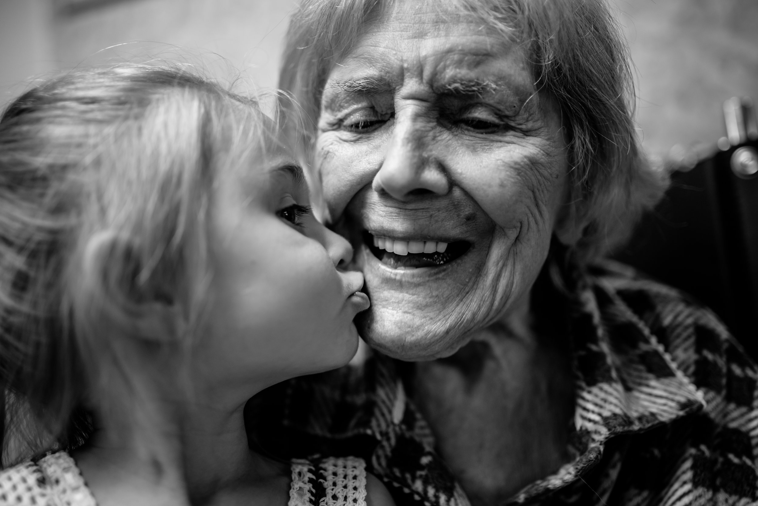 girl kisses great-great-grandmother who smiles