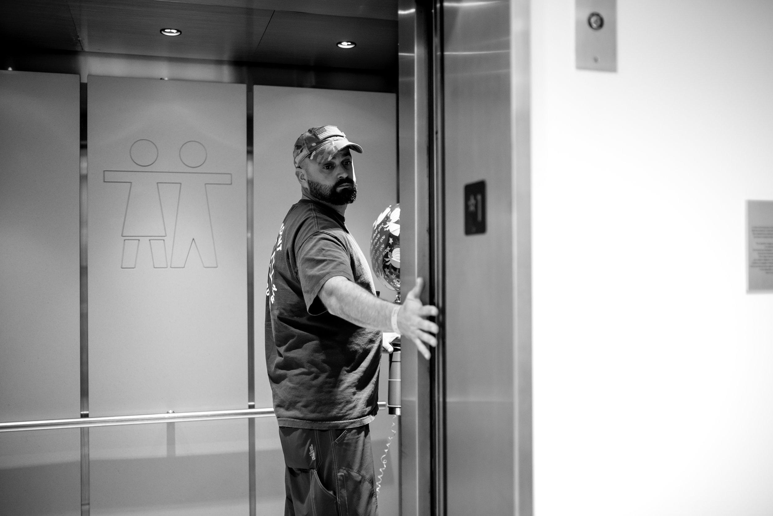 Husband holds hospital elevator door open for wife