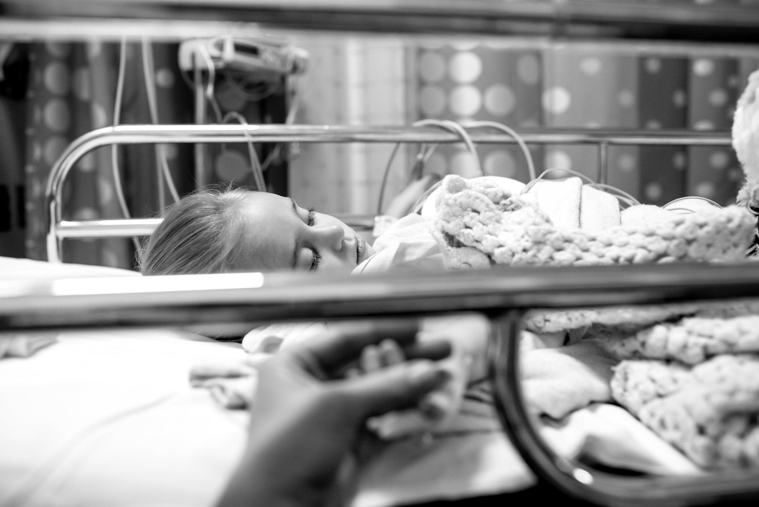 Mom holds daughter's hand after congenital heart defect repair procedure