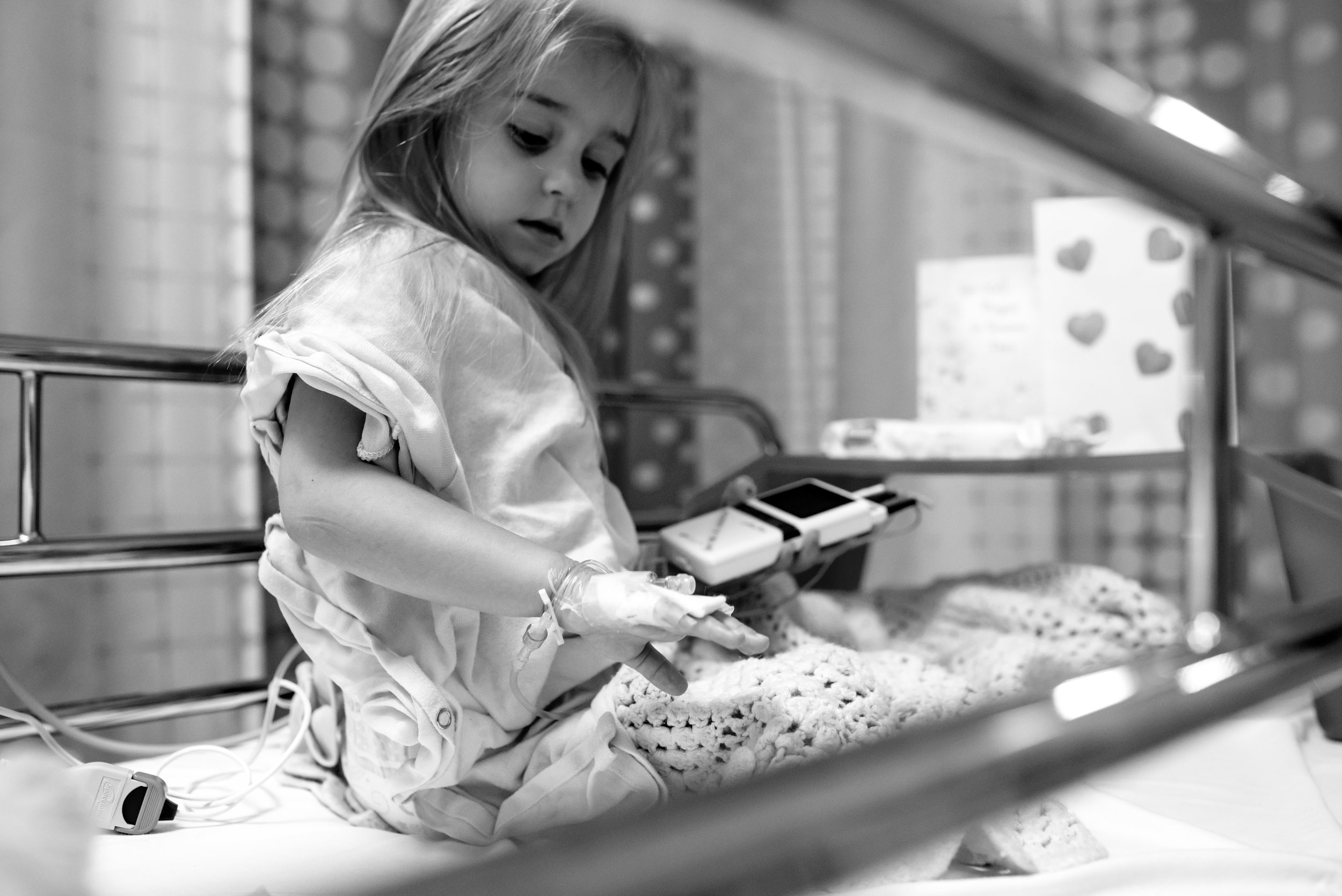 Girl looks at IV port and EKG monitor after congenital heart defect repair procedure