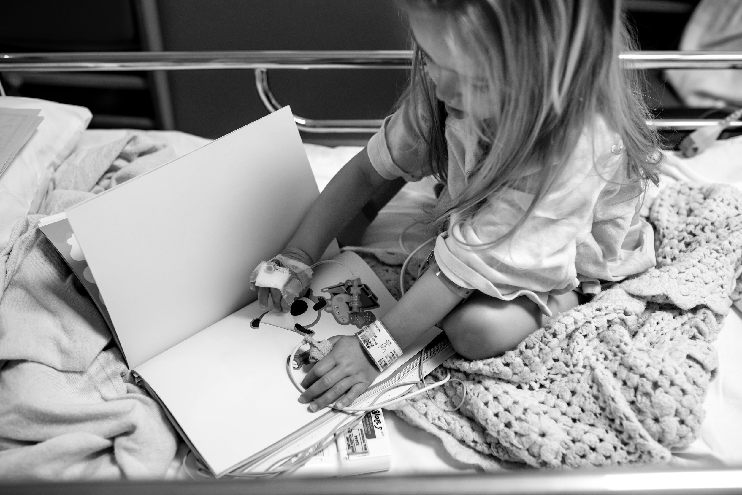 Girl plays with sticker book in observation unit at children's hospital