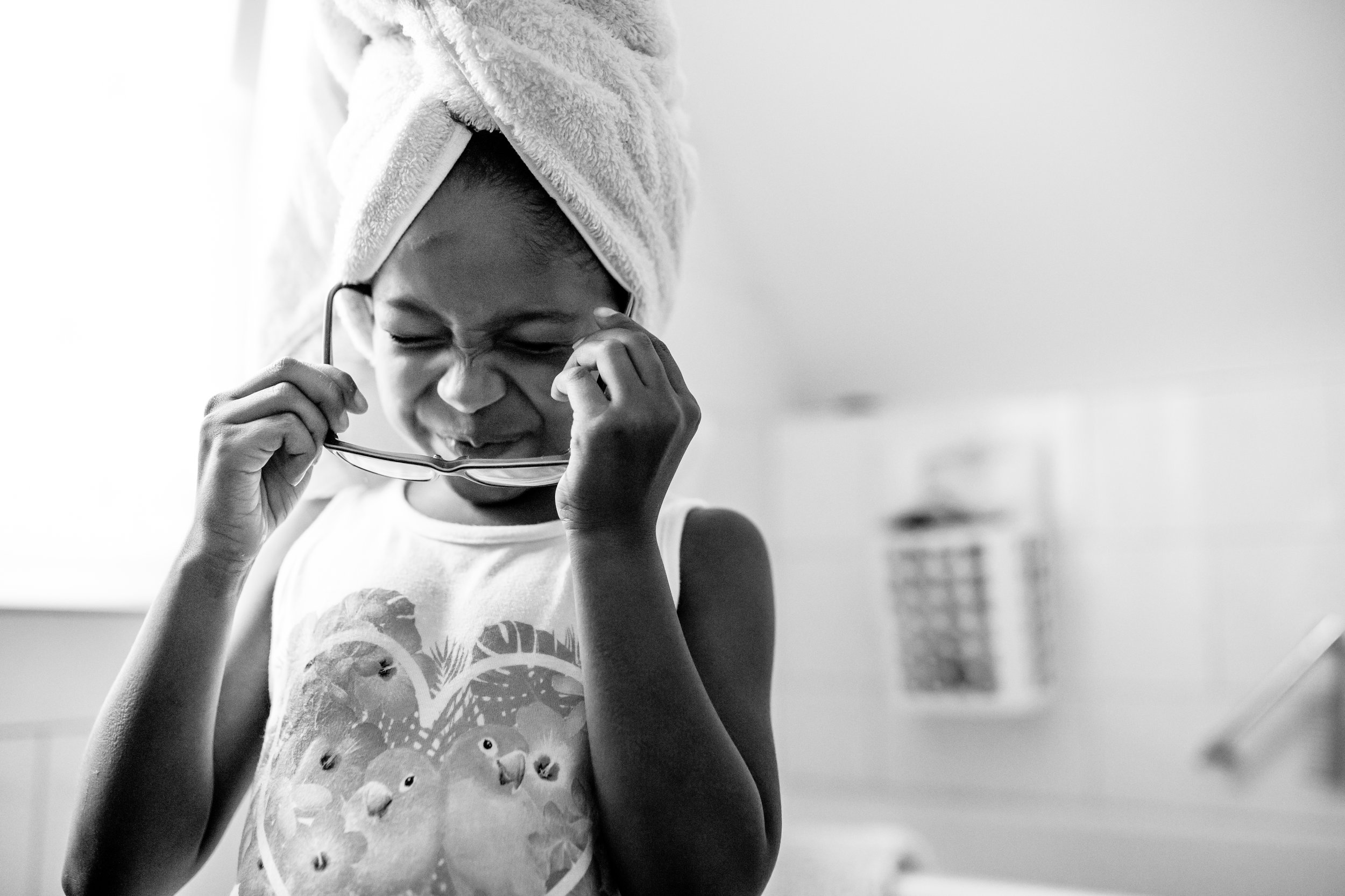 Girl puts on glasses after washing hair