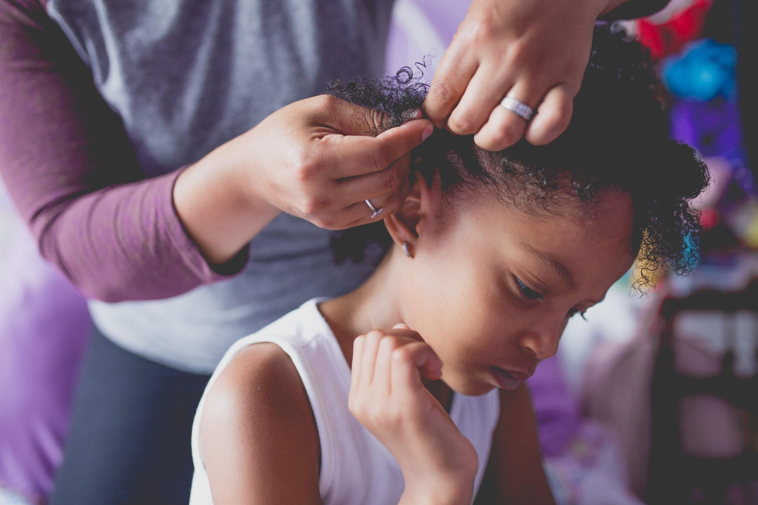 Mom puts cornrow in daughter's hair